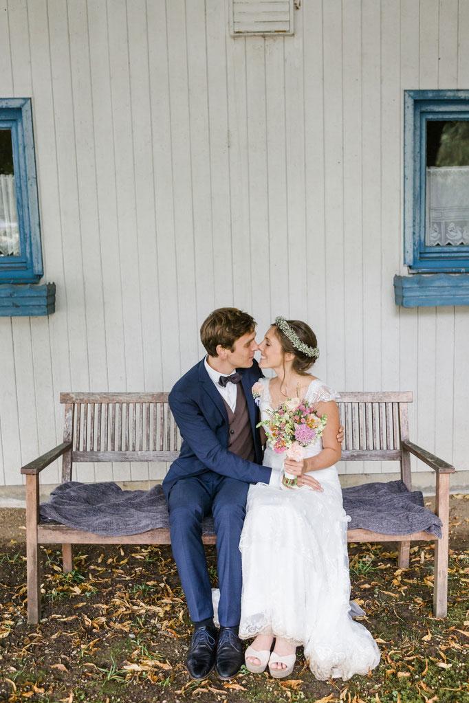 Glückliches Brautpaar küsst sich zärtlich nach der Hochzeitszeremonie