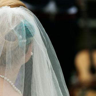 Braut mit Schleier und türkisen Blumen im Haar von hinten