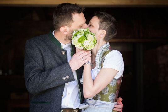 Brautpaar in Tracht küsst sich nach der freien Trauung