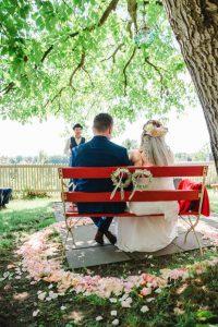 Brautpaar auf einer roten Bank unter Apfelbaum während der freien Trauung