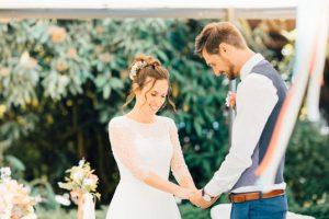 Brautpaar hält sich an den Händen während den Eheversprechen