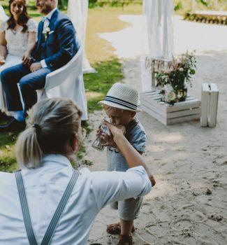 Traurednerin Carolin hilft dem Sohn der Braut während der Zeremonie