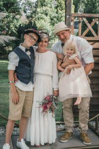 Glückliches Brautpaar mit Kindern am Hochzeitstag