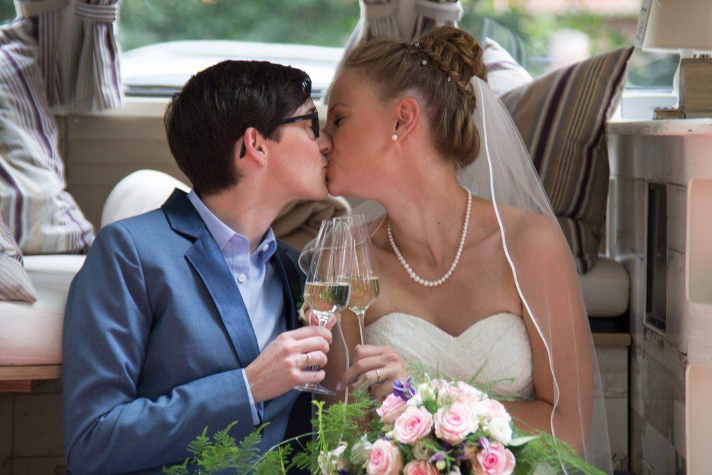 Braut und Braut küssen sich nach der queeren Hochzeit