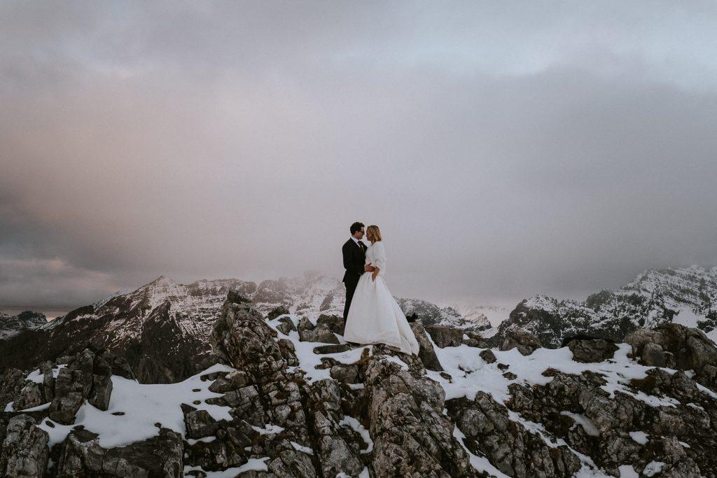 Elopement Hochzeit: Brautpaar auf Bergspitze im Nebel