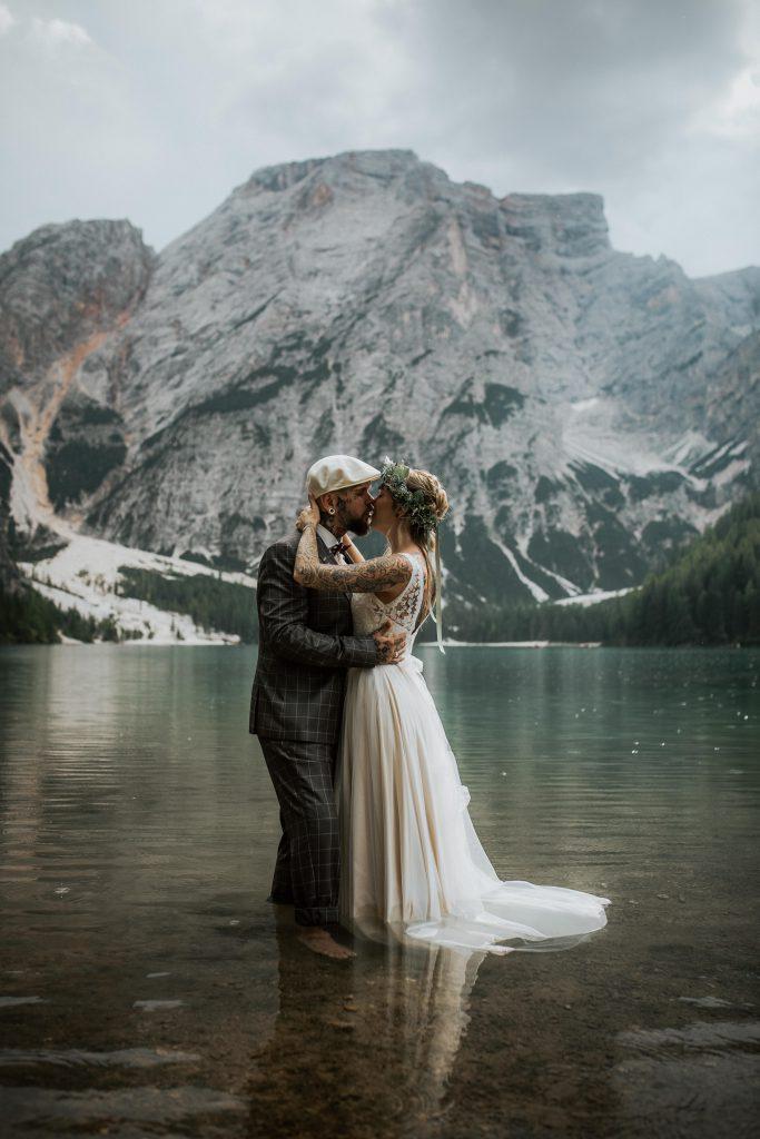 Brautpaar küsst sich mitten in einem einsamen Gebirgssee