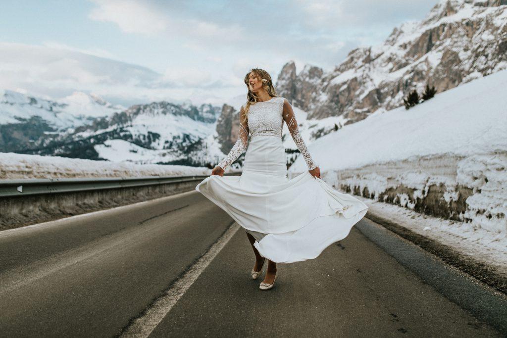 Braut mit Kleid im Boho-Stil mitten in den verschneiten Alpen