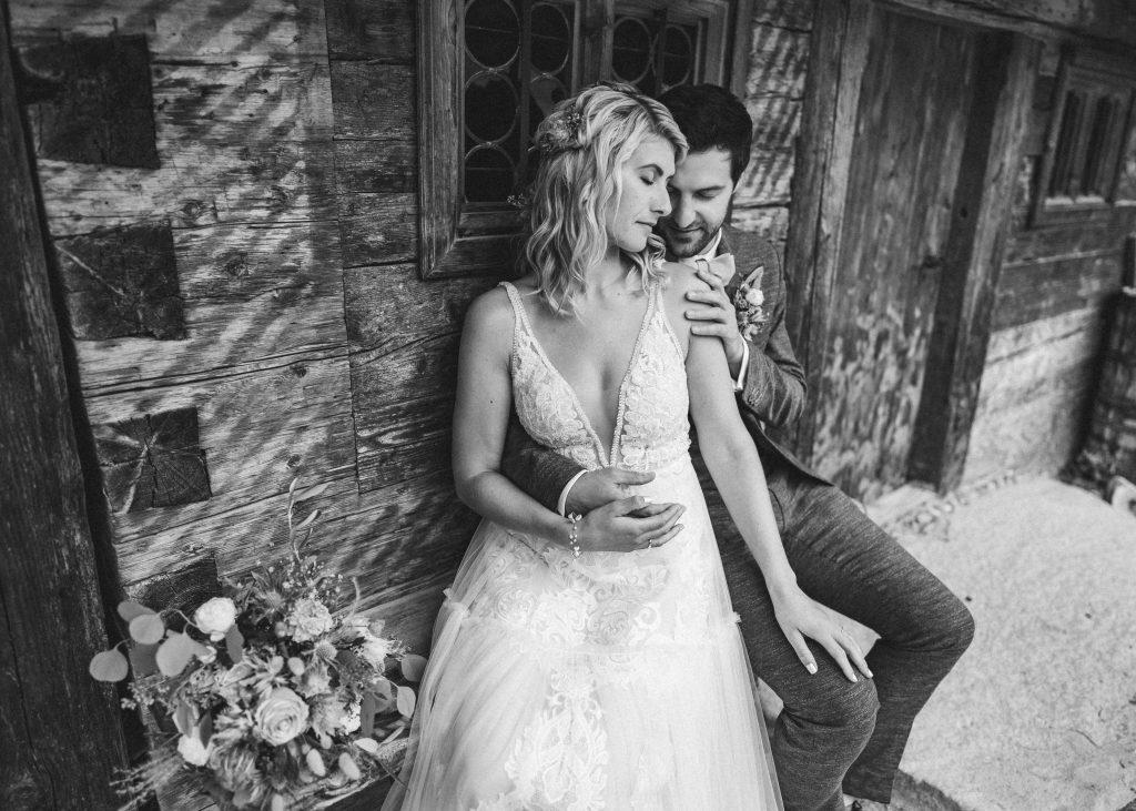 Brautpaar in zärtlicher Umarmung vor Holzhütte