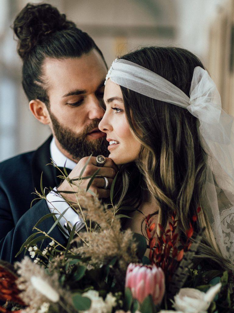 Braut mit Kopfschmuck und Blumen und Bräutigam