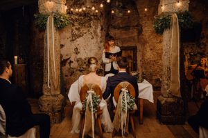 Hochzeitsrednerin Veronika Bracks mit einem Brautpaar in einem Kellergewölbe