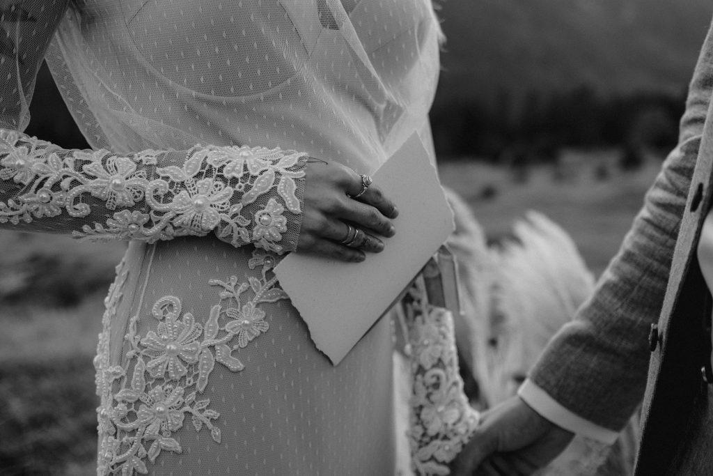 Braut im Boho Brautkleid hält ihr Eheversprechen in der Hand