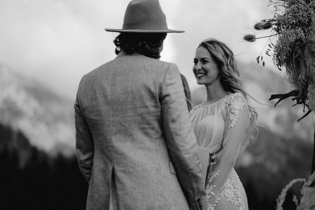 Strahlendes Boho Brautpaar bei der Hochzeit in den Alpen
