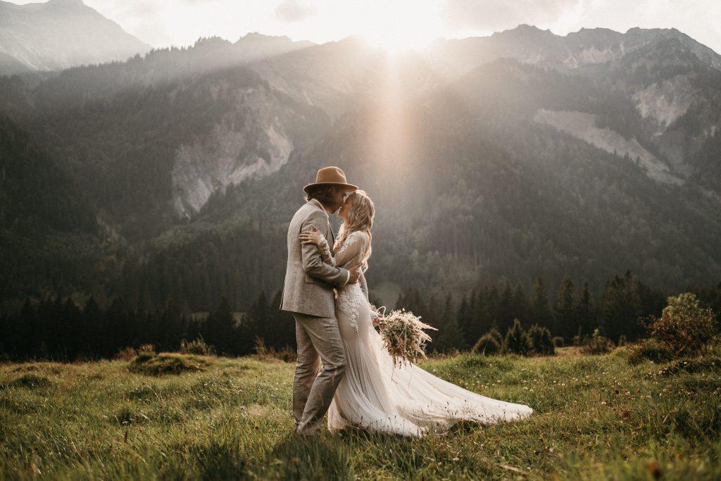 Strahlendes Brautpaar küsst sich beim Sonnenuntergang in den Alpen