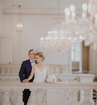 Brautpaar im eleganten Schloss mit Kronleuchtern
