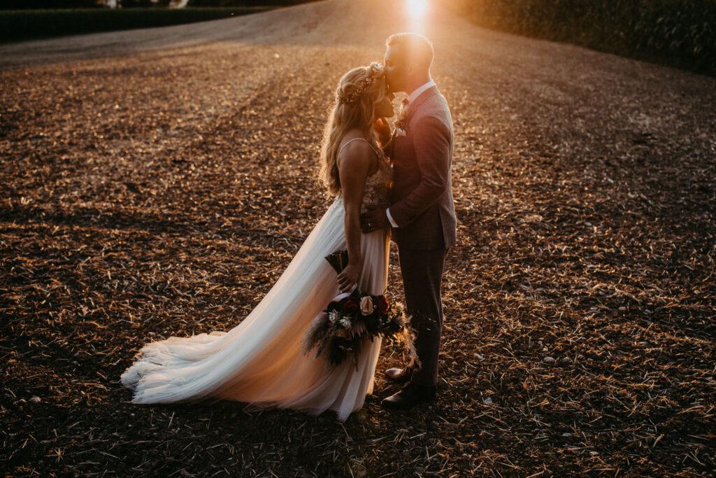 Brautpaar auf Wiese im Sonnenuntergang