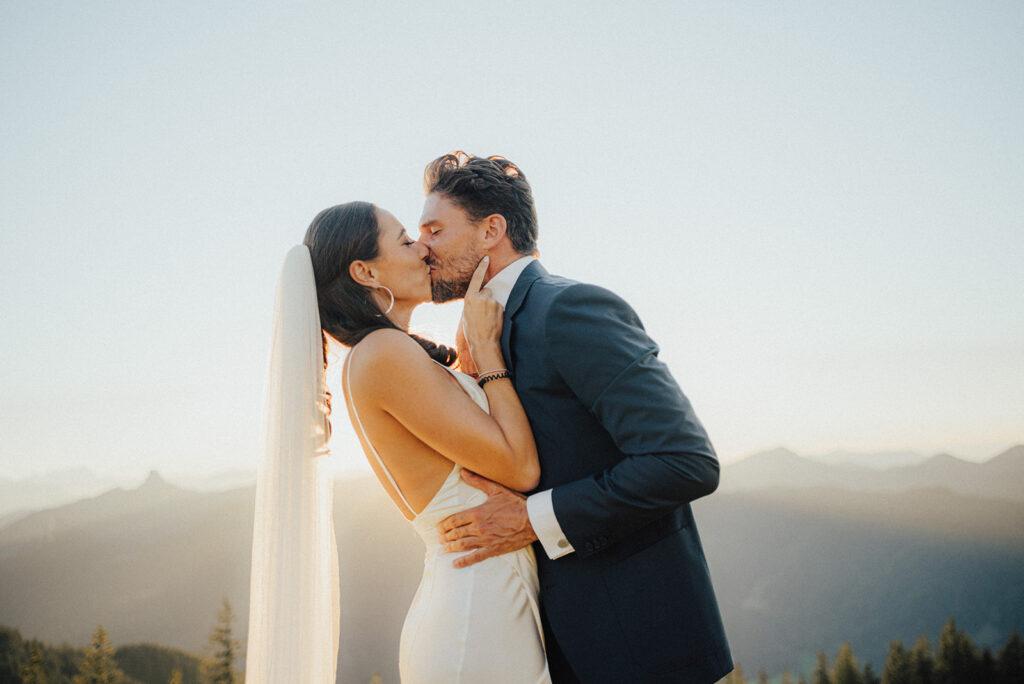 Almhochzeit Braut und Bräutigamküssen sich