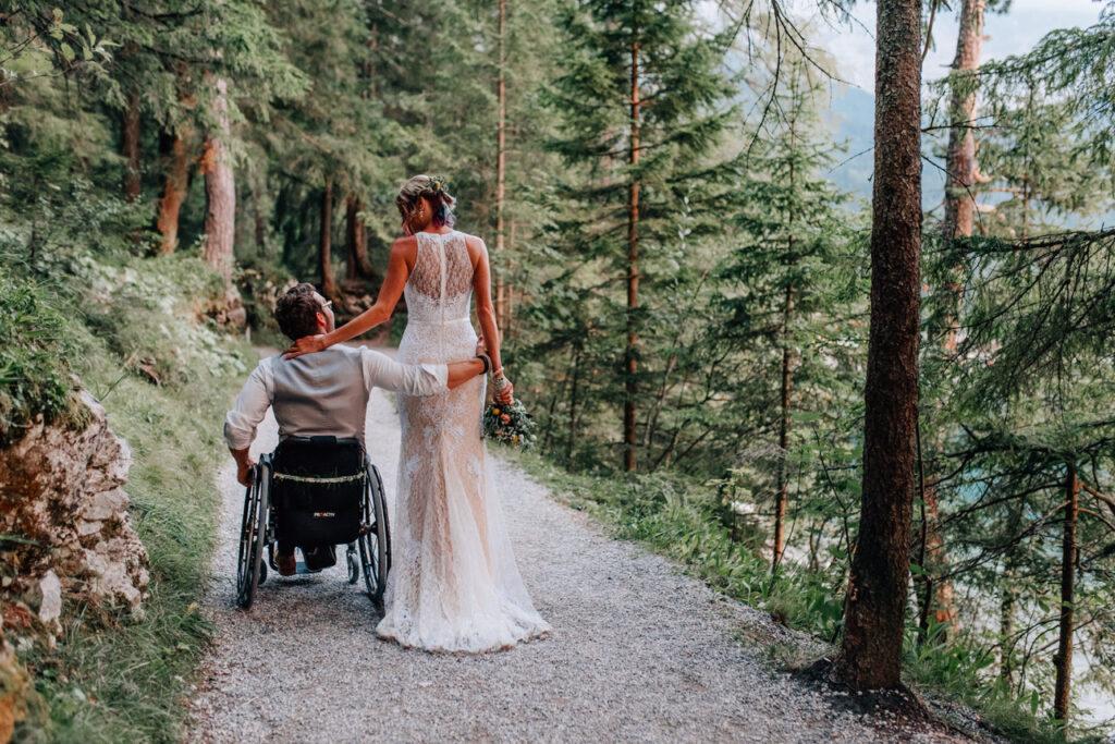 Bräutigam im Rollstuhl spaziert mit seiner Braut durch den Wald